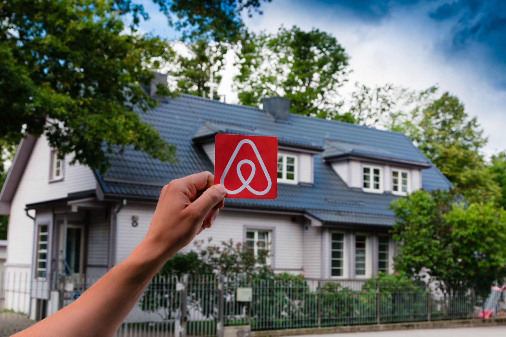 Someone holding an Airbnb sign in front of a house.