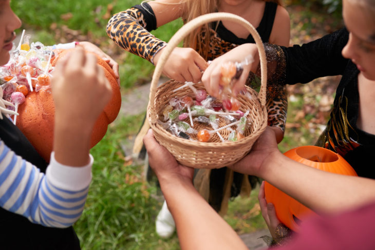 Close-up view of unrecognizable kids in Halloween costumes taking lollipops from basket after trick-or-treating